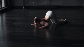 Moça atrativa que faz o esticão em um salão escuro espaçoso Movimento lento filme