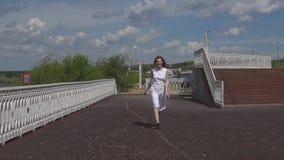 Moça atrativa que salta e que tem o divertimento no parque do verão video estoque