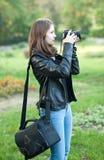 Moça atrativa que toma imagens fora Adolescente bonito na calças de ganga e no casaco de cabedal preto que tomam fotos no parque Fotografia de Stock