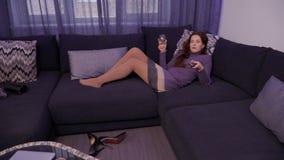 A moça bebe o vinho e o relaxamento em casa olhando a tevê video estoque