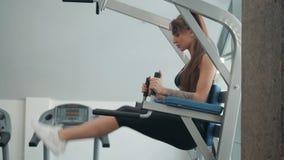 A moça bem treinada e a mulher que treinam os músculos que abdominais fazer se senta levantam no gym filme