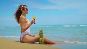 A moça bonita alegre está sentando-se na praia pelo mar com abacaxi e suco video estoque