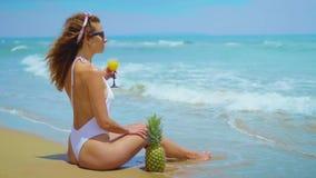 A moça bonita alegre está sentando-se na praia pelo mar com abacaxi e suco vídeos de arquivo