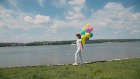 A moça bonita anda com balões à disposição no coustline filme