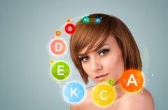 Moça bonita com ícones e símbolos coloridos da vitamina Imagem de Stock