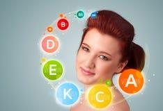 Moça bonita com ícones e símbolos coloridos da vitamina Foto de Stock