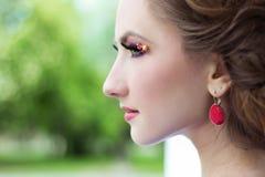 A moça bonita com cabelo bonito e composição do brinco vermelho está na rua na cidade Fotos de Stock