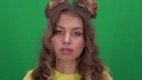 A moça bonita com cabelo louro longo está sorrindo ao olhar na câmera Close-up filme