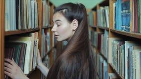 A moça bonita com cabelo preto longo vai entre as prateleiras verticais na biblioteca e sorrisos filme