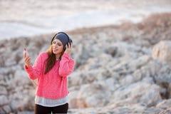 Moça bonita com fones de ouvido e telefone celular fotos de stock royalty free