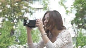 Moça bonita com o cabelo longo, tomando imagens das vistas em um telefone do vintage video estoque