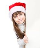 Moça bonita com o chapéu de Santa que está atrás da placa branca Isolado Fotografia de Stock
