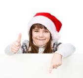 Moça bonita com o chapéu de Santa que está atrás da placa branca Isolado no branco Foto de Stock Royalty Free