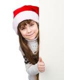 Moça bonita com o chapéu de Santa que está atrás da placa branca no branco Fotografia de Stock