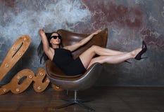 Moça bonita com os óculos de sol que levantam em uma cadeira fotografia de stock