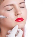 Moça bonita com os bordos vermelhos que obtêm a injeção cosmética nos bordos Isolado no branco Foto de Stock