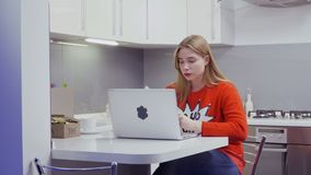 A moça bonita com os bordos vermelhos que vestem a camiseta vermelha usa o portátil na cozinha filme