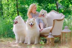 A moça bonita com um cachorrinho branco em seus braços e uns cães macios brancos mais velhos em um sofá retro em um verão jardina Foto de Stock
