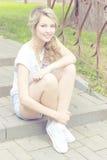 Moça bonita com um sorriso, sentando-se nas escadas no short, sapatilhas em um parque em um dia ensolarado brilhante Fotografia de Stock