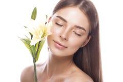 Moça bonita com uma composição natural clara e pele perfeita com as flores em sua mão Face da beleza Foto de Stock Royalty Free