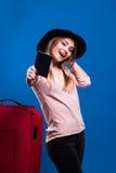 Moça bonita com uma mala de viagem e um passaporte em um fundo azul fotos de stock royalty free