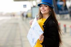 Moça bonita com uma trouxa atrás de seu ombro que guarda um mapa, na rua perto do aeroporto fotos de stock