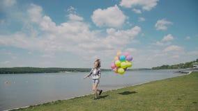 A moça bonita corre com balões à disposição no coustline filme