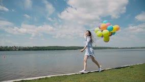 A moça bonita corre e mostra emoções felizes com os balões no coustline video estoque