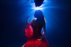 Moça bonita da foto subaquática com vestir longo escuro do cabelo fotografia de stock