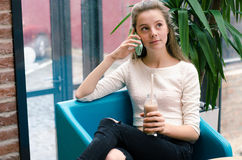 Moça bonita de sorriso que fala no telefone e no cocktail bebendo no café Retrato da mulher de sorriso bonita que senta-se na Fotos de Stock