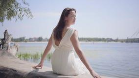 Moça bonita do retrato com o cabelo moreno longo que veste um vestido branco longo da forma do verão que senta-se no video estoque