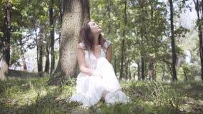 Moça bonita do retrato com o cabelo moreno longo que veste um vestido branco longo da forma do verão que senta-se sob uma árvore  filme
