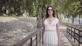 Moça bonita do retrato com os óculos de sol vestindo do cabelo moreno e o vestido branco longo da forma do verão que anda ao long video estoque