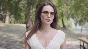 Moça bonita do retrato com os óculos de sol vestindo do cabelo moreno e um vestido branco longo da forma do verão que anda ao lon vídeos de arquivo