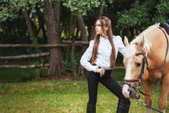 Moça bonita do retrato na camisa branca e em calças pretas com o cavalo seguinte do cabelo longo da beleza no woma elegante da  fotografia de stock