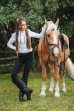 Moça bonita do retrato na camisa branca e em calças pretas com o cavalo seguinte do cabelo longo da beleza no woma elegante da  fotos de stock royalty free