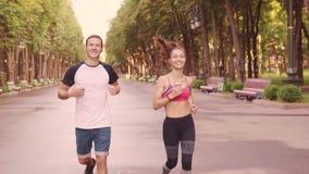 Moça bonita e homens que treinam corridas no parque, movimento lento video estoque