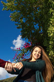 A moça bonita e sorrindo mantém as mãos de puxar do amigo suas e da dançar Fotos de Stock