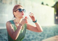 Moça bonita em bolhas de sopro da roupa do vintage imagem de stock royalty free