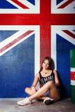 A moça bonita em sapatas dos esportes do short das calças de brim senta-se perto dos tambores no estúdio no fundo da bandeira de  Foto de Stock Royalty Free