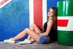 A moça bonita em sapatas dos esportes do short das calças de brim senta-se perto dos tambores no estúdio no fundo da bandeira de  Imagens de Stock Royalty Free