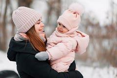 Moça bonita em um fato-macaco cor-de-rosa que joga com sua mãe em um parque nevado do inverno imagem de stock