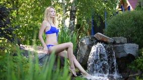 Moça bonita em um maiô que senta-se perto de uma cachoeira artificial no jardim do verão filme