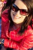 Moça bonita em um revestimento vermelho que senta-se na floresta nos óculos de sol e nos sorrisos Imagem de Stock Royalty Free