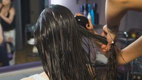 A moça bonita em um salão de beleza para o cabelo obtém o procedimento da saúde filme