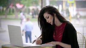 A moça bonita em um terno de negócio que procura um trabalho completa um formulário ou o resumo que olha o portátil senta-se em u filme