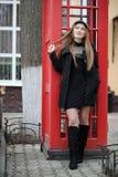 Moça bonita em uma cabine de telefone A menina está falando no th foto de stock royalty free