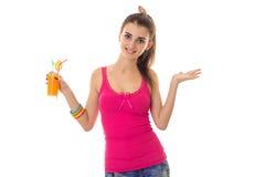 Moça bonita em uma camisa cor-de-rosa que sorri e que realiza em sua mão o suco isolado no fundo branco Fotografia de Stock Royalty Free