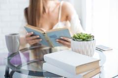 A moça bonita em uma camiseta senta-se na manhã na tabela de vidro, olha-se para fora a janela e lê-se um livro fotos de stock