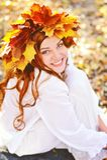 A moça bonita em uma grinalda do amarelo sae, na roupa branca, sentando-se nas folhas da queda em um dia ensolarado e em um riso imagens de stock royalty free